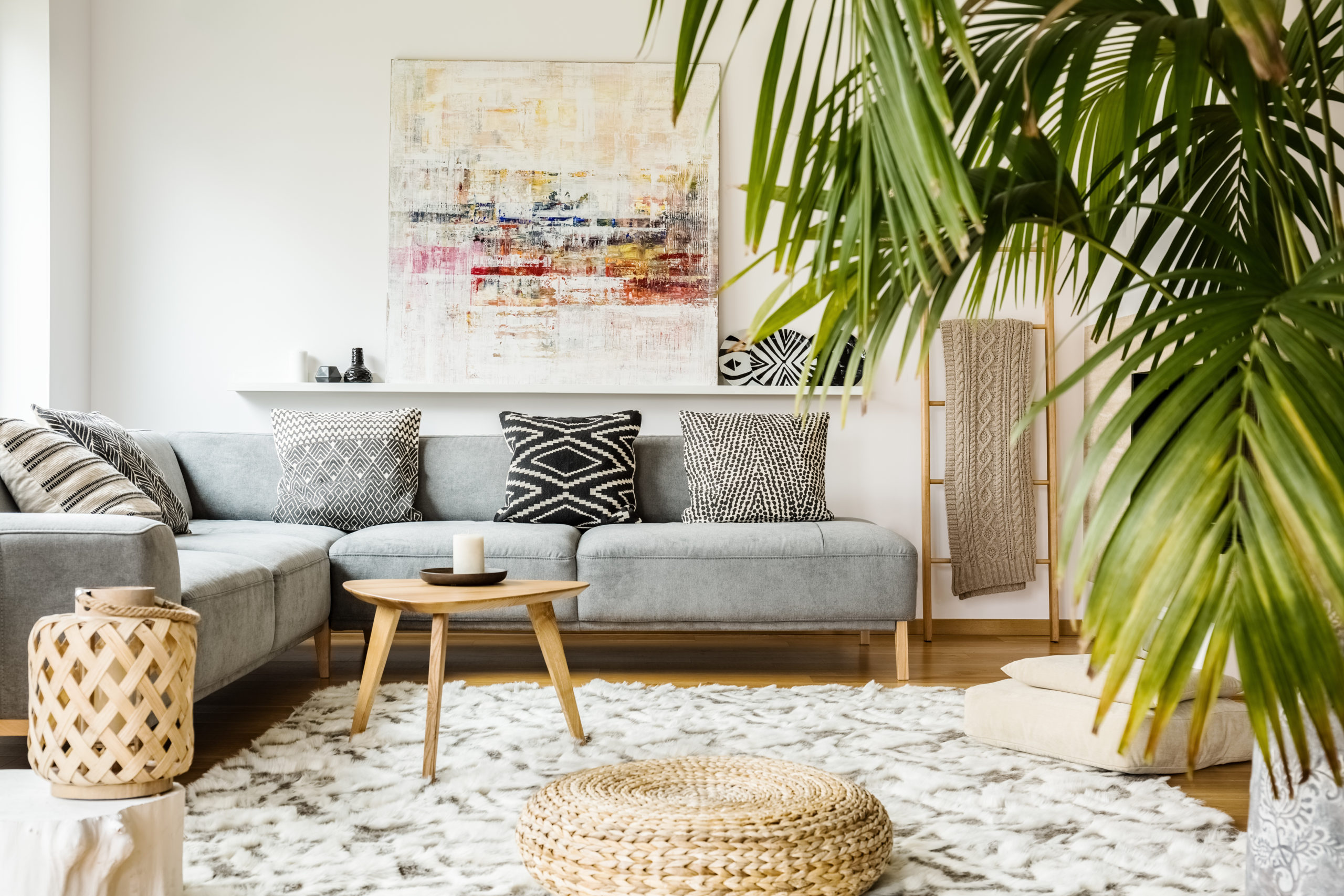 Living room - -Pouf and wooden table in modern living room with painting above grey corner couch